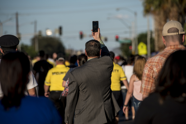 A man holds up his cell phone during the Peace Walk held at the Las Vegas Police Department Convention Center Area Command in Las Vegas on Thursday, June 11, 2015. (Joshua Dahl/Las Vegas Review-Jo ...