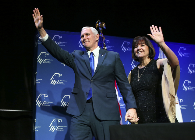 Vice President Mike Pence, with wife Karen, greets the crowd before speaking ahead of a dinner at the Republican Jewish Coalition's annual leadership meeting at the Venetian hotel-casino in Las Ve ...