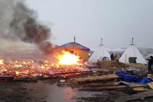 Dakota Access pipeline opponents burn structures in their main protest camp in southern North Dakota near Cannon Ball, N.D., on Wednesday, Feb. 22, 2017, as authorities prepare to shut down the ca ...