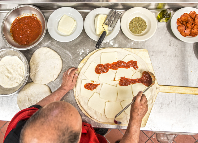 Chef/co-owner John Arena adds Italian tomato sauce while preparing an Olde New York specialty pizza, made with thick slices of mozzarella, old school pepperoni, basil  and pecorino romano cheese,  ...