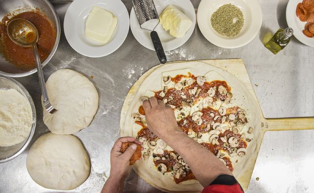 Chef/co-owner John Arena prepares an Olde New York specialty pizza, made with thick slices of mozzarella, old school pepperoni, basil, Italian tomato sauce and pecorino romano cheese, on Thursday, ...