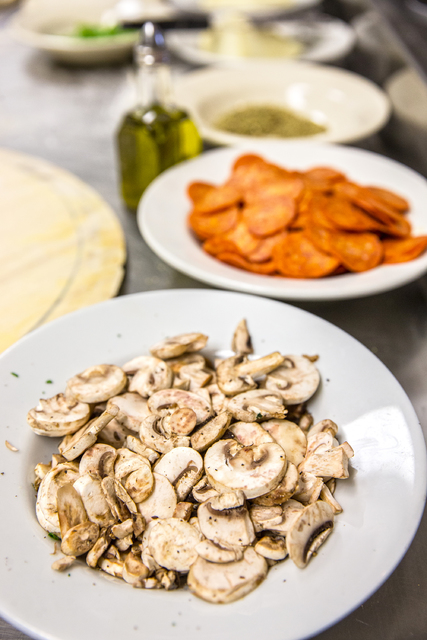 Fresh ingredients laid out to prepare an Olde New York specialty pizza, including mushrooms, thick slices of mozzarella, old school pepperoni, basil, Italian tomato sauce and pecorino romano chees ...
