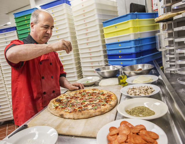 Chef/co-owner John Arena adds fresh basil to an Olde New York specialty pizza, with dozens of trays of pizza dough on Thursday, Feb. 2, 2017, at Metro Pizza, in Henderson.  (Benjamin Hager/Las Veg ...