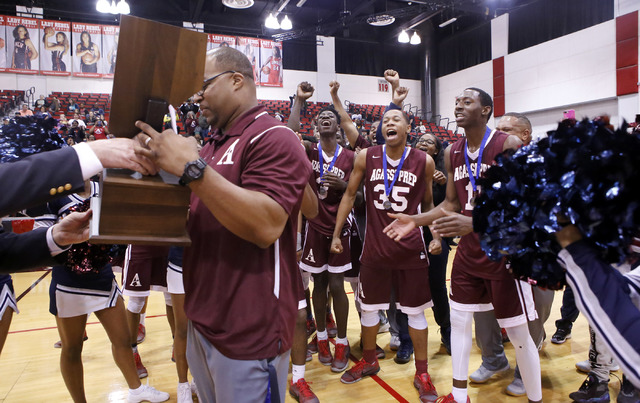 Agassi Prep head coach Trevor Diggs, left, accepts the state championship trophy as his players cheer at the Cox Pavilion on Saturday, Feb. 25, 2017, in Las Vegas. Agassi Prep defeated Adelson Sch ...