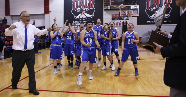 Needle players react as their head coach Manuel Calderon accepts a trophy after winning a Class 2A girls state final championship game at the Cox Pavilion on Saturday, Feb. 25, 2017, in Las Vegas. ...