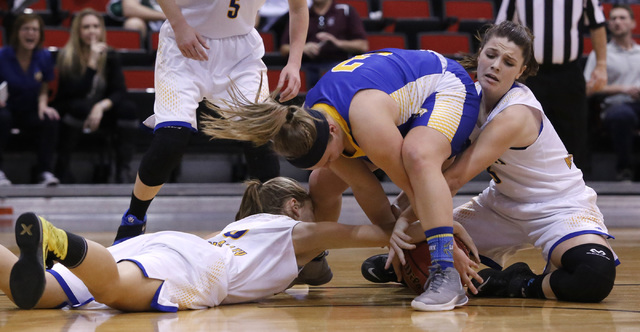 Lowry's Alyssa Kuskie (3), center, struggles for a loose ball from Moapa Valley players during the first half of a Class 3A girls state semifinal game at the Cox Pavillion Center on Friday, Feb. 2 ...