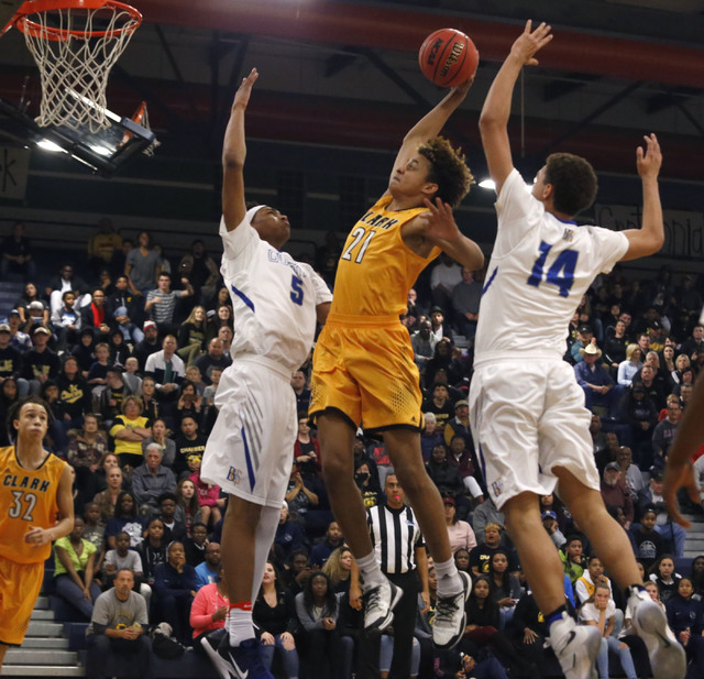 Clark's Jalen Hill (21) dunks over Bishop Gorman's Chuck O'Bannon (5) and Bishop Gorman's Saxton Howard (14) during the first half of a Class 4A Sunset Region championship boys basketball game on  ...