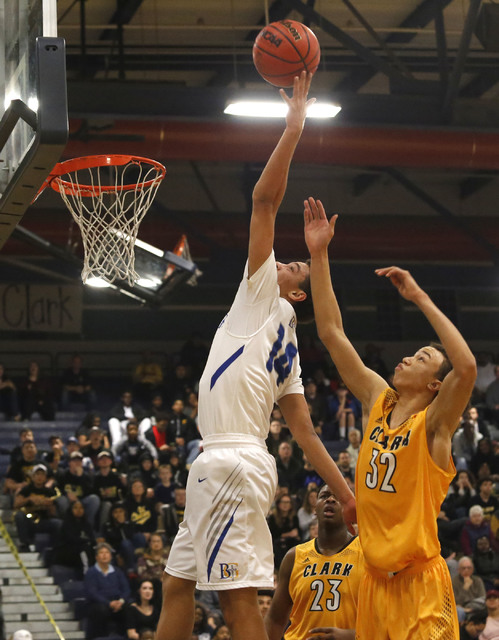 Bishop Gorman's Saxton Howard (14) grabs a rebound over Clark's Ian Alexander (32) and Clark's Antwon Jackson (23) during the first half of a Class 4A Sunset Region championship boys basketball ga ...