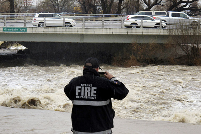 A Sparks firefighter takes a picture of the rising Truckee River, Sunday, Jan. 8, 2017, where it runs near the Grand Sierra hotel-casino along a line that divides the cities of Reno and Sparks. (A ...