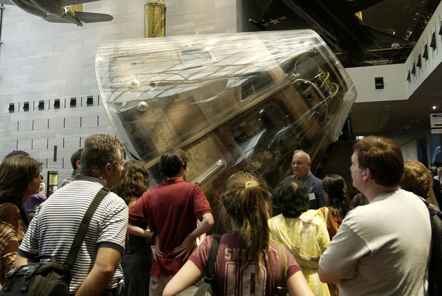 Visitors gather around the Apollo 11 Command Module inside the Air and Space museum in Washington, D.C., July 20, 2004. (NASA via AP)