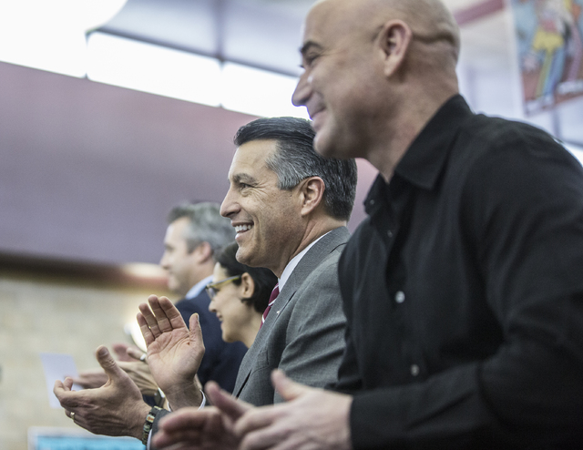 Nevada Gov. Brain Sandoval, middle, and Andre Agassi, right, clap for students during a press conference to announce that Democracy Prep Public Schools will assume school operations of Andre Agass ...