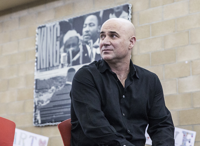 Andre Agassi listens to Nevada Gov. Brain Sandoval speak during a press conference to announce that Democracy Prep Public Schools will assume school operations of Andre Agassi Preparatory Academy  ...