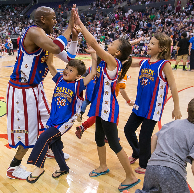 Scooter Christensen high fives young fans. (Photo courtesy of Harlem Globetrotters)
