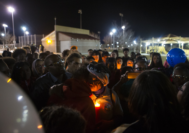Wanda Dunmore, center right, comforts the girlfriend of Shadow Ridge High School student Tiris Coleman Jr, who was killed in a shooting this past Sunday, during a vigil at Aviary Park in North Las ...