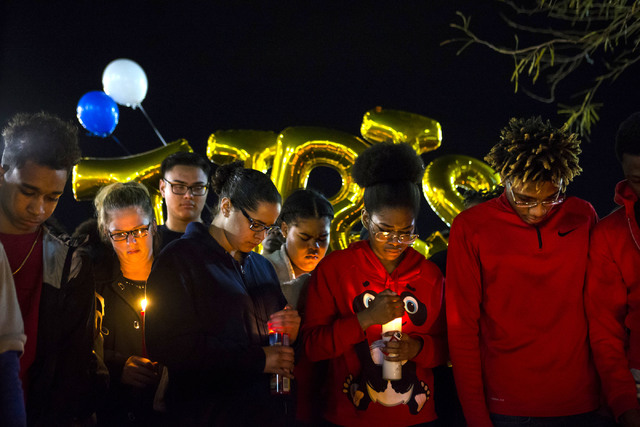 People pause for a moment of silence during a vigil for Shadow Ridge High School student Tiris Coleman Jr, who was killed in a shooting this past Sunday, at Aviary Park in North Las Vegas on Tuesd ...