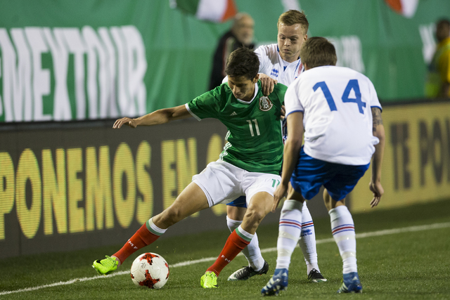 Mexico's Jurgen Damm (11) moves with the ball under pressure from Iceland's Bodvar Bodvarsson (14) in the men's soccer exhibition match at Sam Boyd Stadium on Wednesday, Feb. 8, 2017, in Las Vegas ...