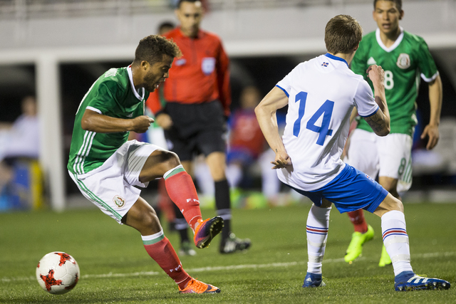 Mexico's Giovani Dos Santos (10) makes a pass under pressure from Iceland's Bodvar Bodvarsson (14) in the men's soccer exhibition match at Sam Boyd Stadium on Wednesday, Feb. 8, 2017, in Las Vegas ...