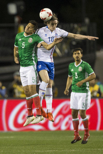 Mexicoճ Jesus Molina (5) and Icelandsճ Daniel Leo Gretarsson (18) jump for the ball in the men's soccer exhibition match at Sam Boyd Stadium on Wednesday, Feb. 8, 2017, in Las Vegas. M ...
