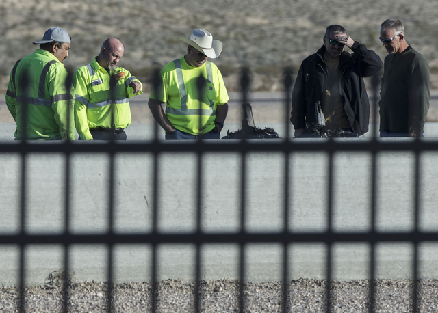 Investigators and track officials look over the remains of the Lamborghini Gallardo that crashed on Sunday killing an instructor and driver at SpeedVegas. Photo taken on Monday, Feb. 13, 2017, at  ...