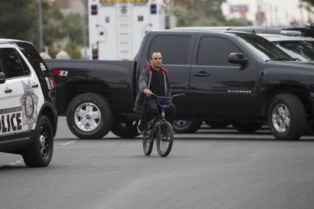 A man rides his bike near police activity on Rainbow Boulevard and Cheyenne Avenue on Saturday, Feb. 25, 2017, in Las Vegas. (Erik Verduzco/Las Vegas Review-Journal) @Erik_Verduzco