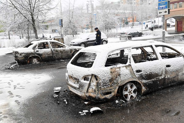 In this picture taken on Monday, Feb. 20, 2017, a policeman investigates a burned out car in the suburb of Rinkeby outside Stockholm. Police in Sweden said Tuesday they were investigating riots th ...