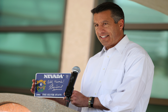Gov. Brian Sandoval shows a signed Nevada license plate in contribution to a time capsule during an event to commemorate Nevada's Sesquicentennial with the burial of a time capsule at the Nevada S ...