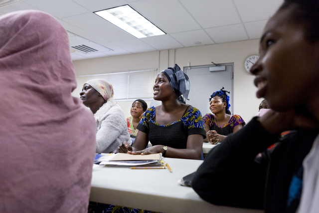 Jadija Irakoze, center, reugee and student of the Beginners ESL class at Catholic Charities of Southern Nevada, North Las Vegas Blvd. and North Owens Ave., writes the month June on the board, Las  ...