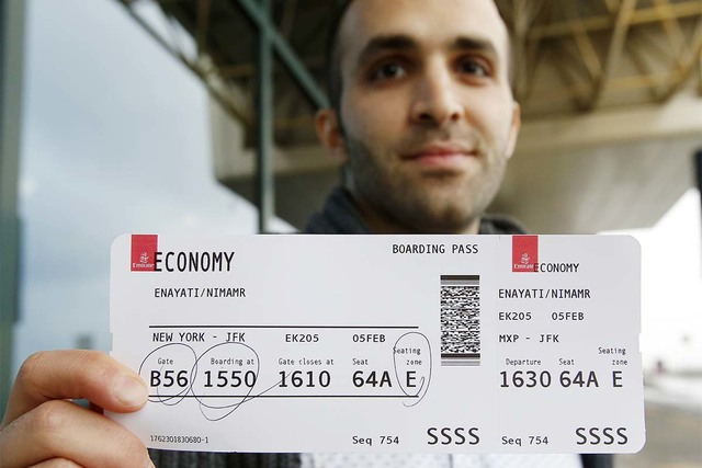 Iranian-born bioengineer researcher Nima Enayati holds up his boarding pass at the Milan's Malpensa International airport in Busto Arsizio, Italy, Sunday, Feb. 5, 2017. Just hours after an appeals ...