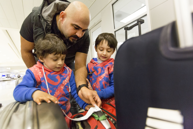 Dhulifiqar Naqvi, refugee from Iraq, checks his brother's luggage with his nephews after his brother and family arrived from Iraq in wake of Trump's travel ban, McCarran International Airport, Las ...