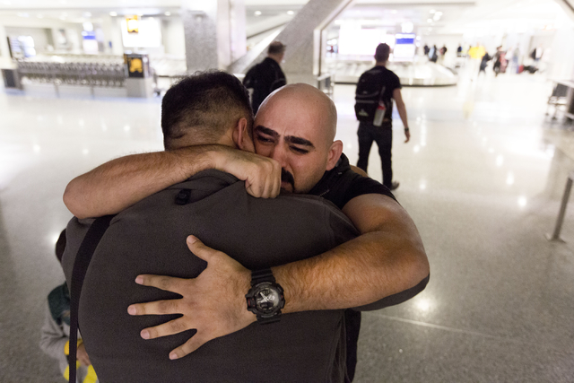 A tearful Dhulifiqar Naqvi, right, a refugee from Iraq who had arrived in the United States 10 months ago, reunites with his brother Saif Naqvi, who arrived with his wife and children in wake of T ...