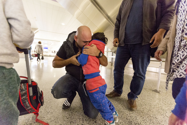 A tearful Dhulifiqar Naqvi, right, a refugee from Iraq who had arrived in the United States 10 months ago, reunites with his nephew Mohammad Saif and his brother's family in wake of Trump's travel ...