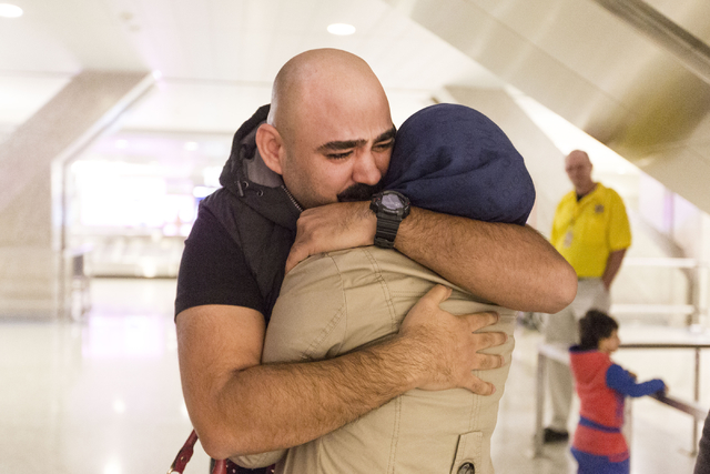 A tearful Dhulifiqar Naqvi, right, a refugee from Iraq who had arrived in the United States 10 months ago, reunites with his sister-in- law, Jamila Saif Naqvi, who arrived with her husband and chi ...