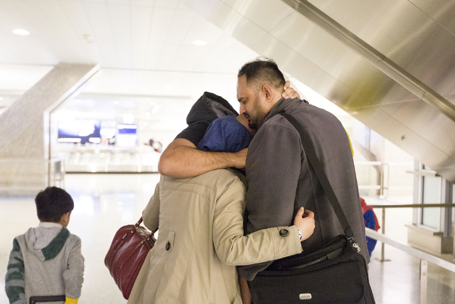 A tearful Dhulifiqar Naqvi, rear, a refugee from Iraq who had arrived in the United States 10 months ago, reunites with his brother Saif Naqvi, who arrived with his wife and children in wake of Tr ...