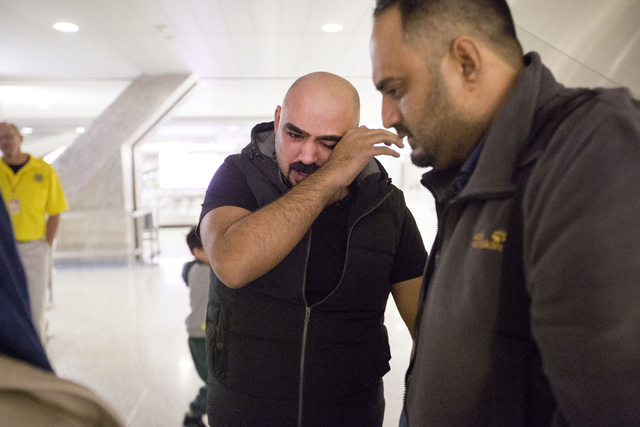 A tearful Dhulifiqar Naqvi, left, a refugee from Iraq who had arrived in the United States 10 months ago, reunites with his brother Saif Naqvi, who arrived with his wife and children in wake of Tr ...