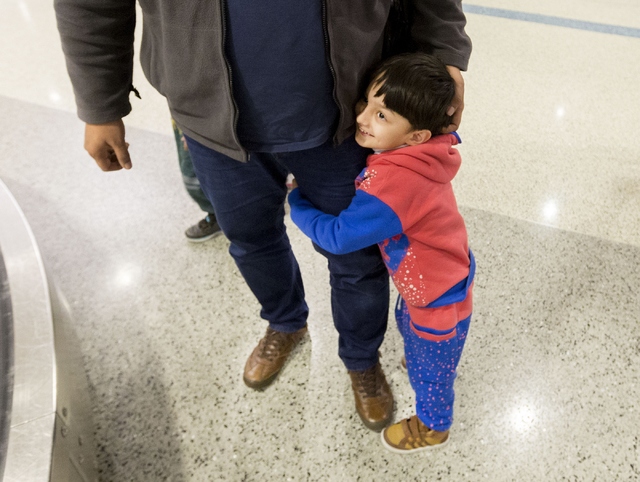 Mohammad Saif, 3, holds onto his father's, leg after they reunited with their family at the McCarran International Airport, Las Vegas, Feb. 10, 2017, in wake of Trump's travel ban. (Elizabeth Brum ...