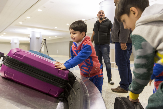 Mohammad Saif, 3, a refugee from Iraq, looks for his family's luggage with excitement as his uncle Dhulifiqar Naqvi, who had arrived 10 months prior talks with his brother Saif Naqvi who arrived w ...