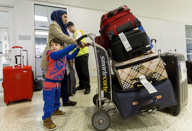 Jamila Saif, refugee from Iraq, and her son, Mohammad, 3, gather their luggage at  McCarran International Airport, Las Vegas, Feb. 10, 2017, in wake of Trump's travel ban.  (Elizabeth Brumley/Las  ...