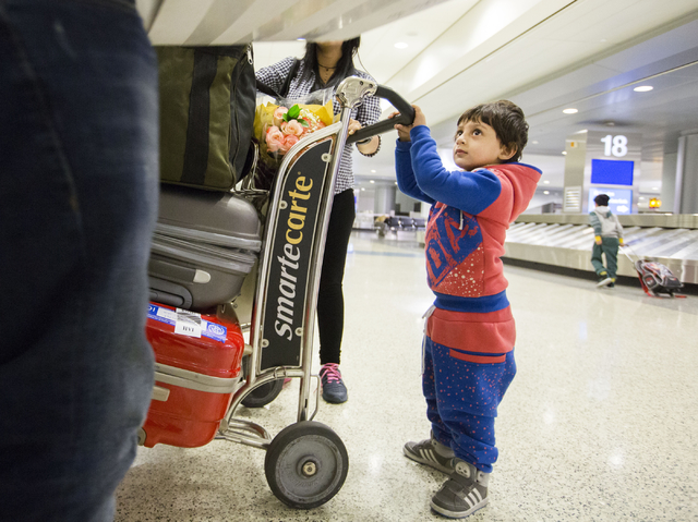 Muhammad Saif, 3, a refugee from Iraq, holds onto his families luggage as they arrive to McCarran International Airport, Las Vegas, Feb. 10, 2017, in wake of Trump's travel ban.  (Elizabeth Brumle ...