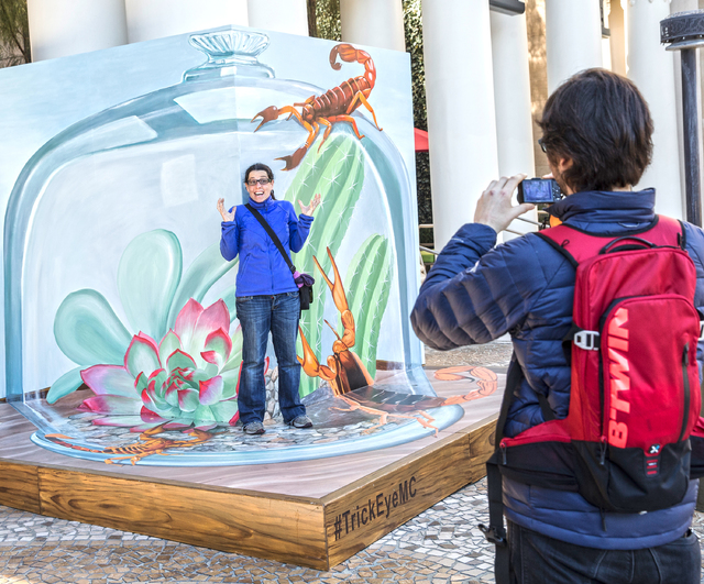 Montse Arango, left, has her photo taken by Emilio Sanchez in front of a Trick Eye Experience painting, one of a set of 3-D interactive art installations outside the Monte Carlo hotel-casino, on T ...
