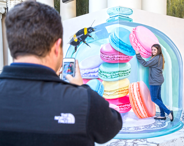 Leslie Brignac, right, poses for a photo taken by husband Kalib Brignac, in front of a Trick Eye Experience painting, one of a set of 3-D interactive art installations outside the Monte Carlo hote ...