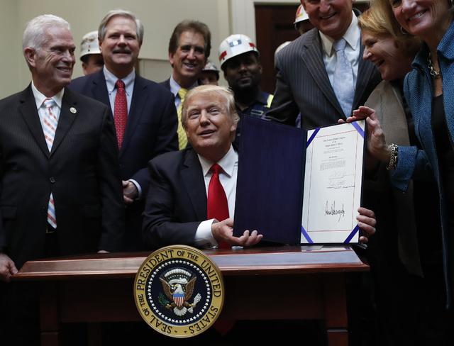 President Donald Trump, joined by coal miners and members of congress including Rep. Bill Johnson, R-Ohio, Rep. Jim Renacci, R-Ohio, Sen. Joe Manchin, D-W.Va., Sen. Heidi Heitkamp, D-N.D., and Sen ...