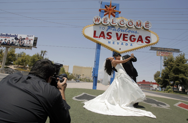 Wedding photographer Sergio Lopez, left, take pictures of newlyweds Joseph Buangan and his wife, Joyce, of Torrance, Calif., with the Welcome to Fabulous Las Vegas sign in the background Saturday, ...