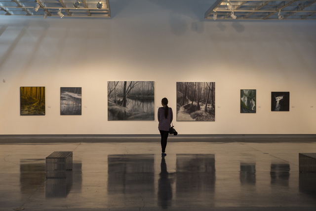 """Chada Kate-Kaew looks at paintings in the """"Transmutations: Robert Beckmann Under the Western Sky 1977-2017"""" exhibition at Sahara West Library in Las Vegas on Tuesday, Jan. 31, 2017. (Chase Stevens ..."""