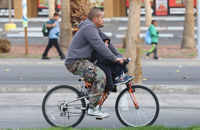 A man rides his bicycle with a child on Swenson Avenue, Tuesday, Feb. 21, 2017, in Las Vegas. (Bizuayehu Tesfaye/Las Vegas Review-Journal) @bizutesfaye