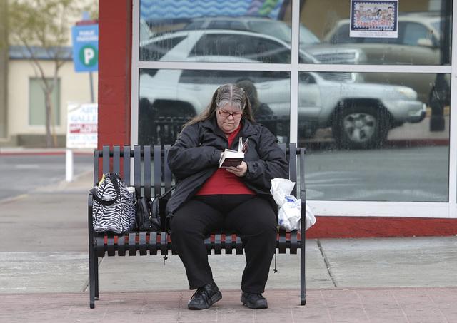 Kimberly Jones of Henderson reads her book as she waits for a bus on Water Street on Monday, Feb. 6, 2017, in Henderson. (Bizuayehu Tesfaye/Las Vegas Review-Journal) @bizutesfaye