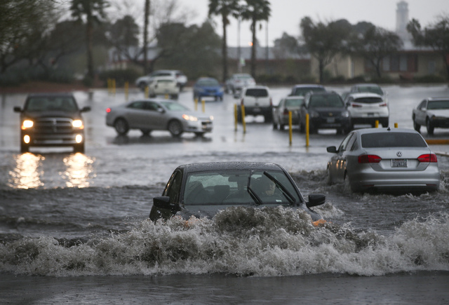 People navigate a flooded parking lot at UNLV in Las Vegas on Saturday, Feb. 18, 2017. (Chase Stevens/Las Vegas Review-Journal) @csstevensphoto