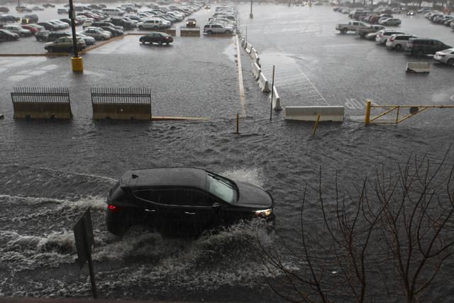 People navigate a flooded parking lot at UNLV in Las Vegas on Saturday, Feb. 18, 2017. (Chase Stevens/Las Vegas Review-Journal) @csstevensphoto