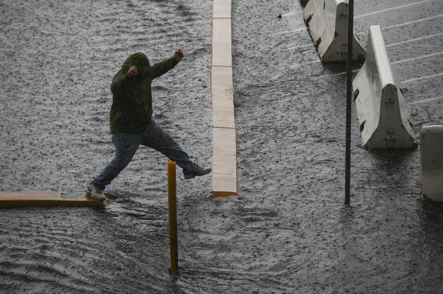 A man navigates a flooded parking lot at UNLV in Las Vegas on Saturday, Feb. 18, 2017. (Chase Stevens/Las Vegas Review-Journal) @csstevensphoto