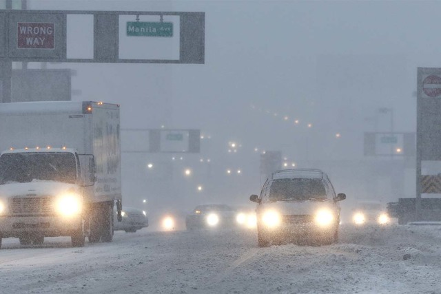 Vehicles drive drive through snow as they approach the Holland Tunnel, Thursday, Feb. 9, 2017, in Jersey City, New Jersey. A powerful, fast-moving storm swept through the northeastern U.S. early T ...