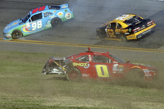 Garrett Smithley (0), Aric Almirola (98) and Brendan Gaughan (62) are involved in a multi-car crash during a NASCAR Xfinity series auto race at Daytona International Speedway in Daytona Beach, Fla ...